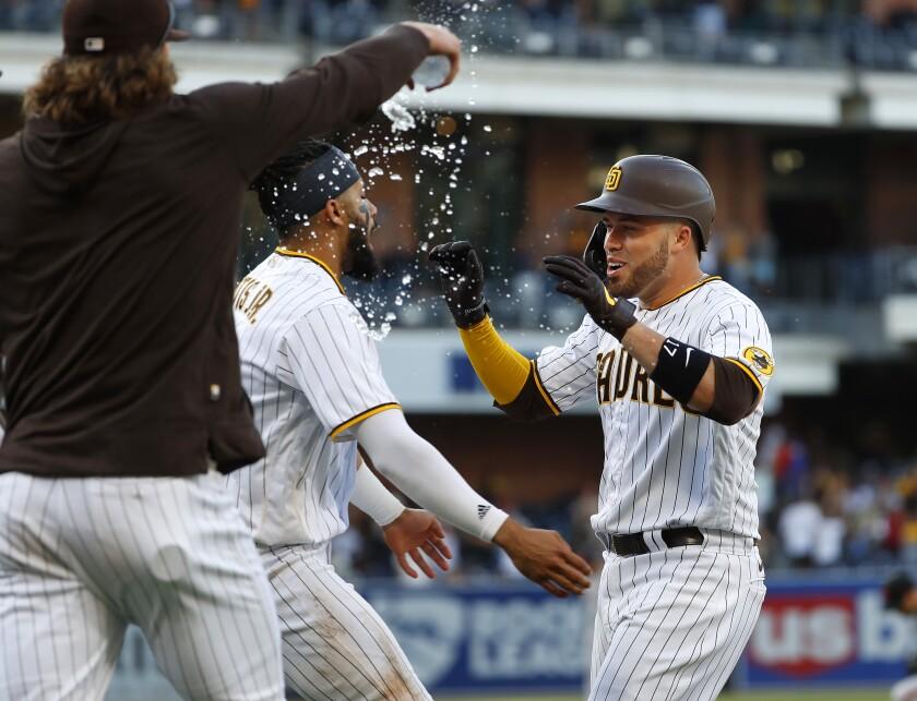Padres' Victor Caratini celebrates with teammates after the winning hit scoring Jurickson Profar.