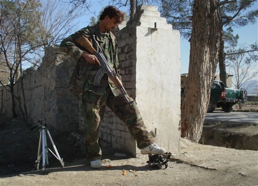 An Afghan security officer steps on a wreckage of the suicide attacker's car near U.S. Forward Operating Base Chapman in the city of Khost, Afghanistan, Monday, Jan. 19, 2009. A suicide car bomb attack near the gates of a U.S. base in eastern Afghanistan on Monday killed one Afghan and wounded seve