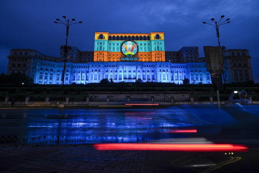 A Euro 2020 video mapping is projected on the facade of the communist era built Palace of Parliament, formerly known as the House of the People, in Bucharest, Romania, Friday, June 11, 2021, two days before the city hosts its first game between Austria and North Macedonia. (AP Photo/Vadim Ghirda)