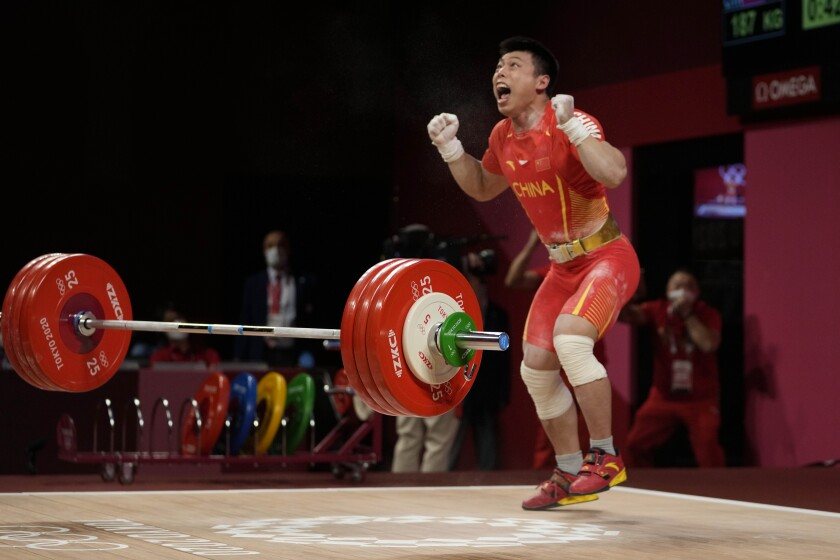 Chen Lijun of China celebrates after winning the gold medal and setting an Olympic record in the men's 67kg weightlifting event, at the 2020 Summer Olympics, Sunday, July 25, 2021, in Tokyo, Japan. (AP Photo/Luca Bruno)