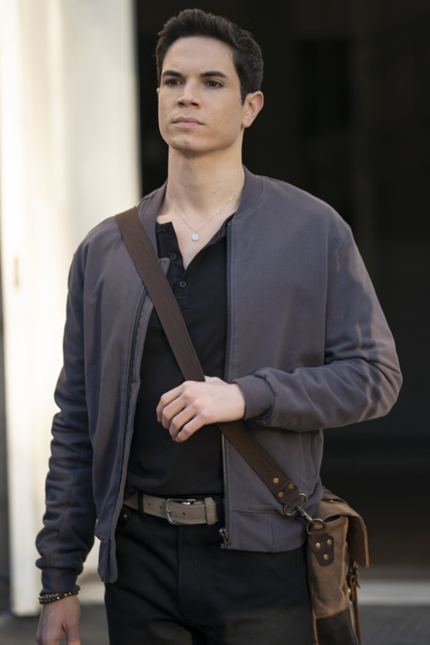 A man in a black shirt and a gray cardigan with a leather bag slung over his shoulder