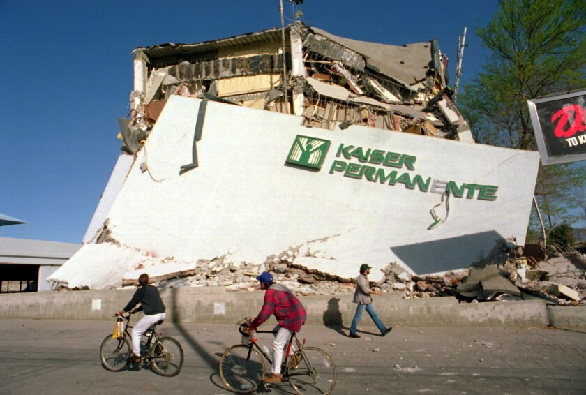 Cyclists roll past the remains of a Kaiser Permanente clinic and office building in Granada Hills that collapsed during the Northridge earthquake of 1994.