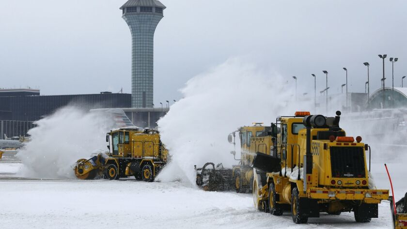 Snowplows clear snow along runways and the tarmac at Chicago O'Hare International Airport on Jan. 28, 2019.