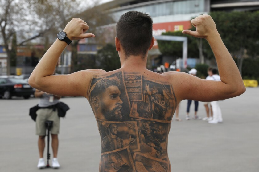 FILE - In this Friday, Aug. 6, 2021 file photo, a Barcelona fan poses showing tattoos of Lionel Messi and other Barcelona players before FC Barcelona club President Joan Laporta gives a news conference in Barcelona, Spain. Barcelona's first season without Lionel Messi after nearly two decades starts with a home match against Real Sociedad on Sunday Aug. 15, 2021. The fans are still adjusting to the loss of the club's greatest player. Messi signed a two-year contract with Paris Saint-Germain. (AP Photo/Joan Monfort, File)