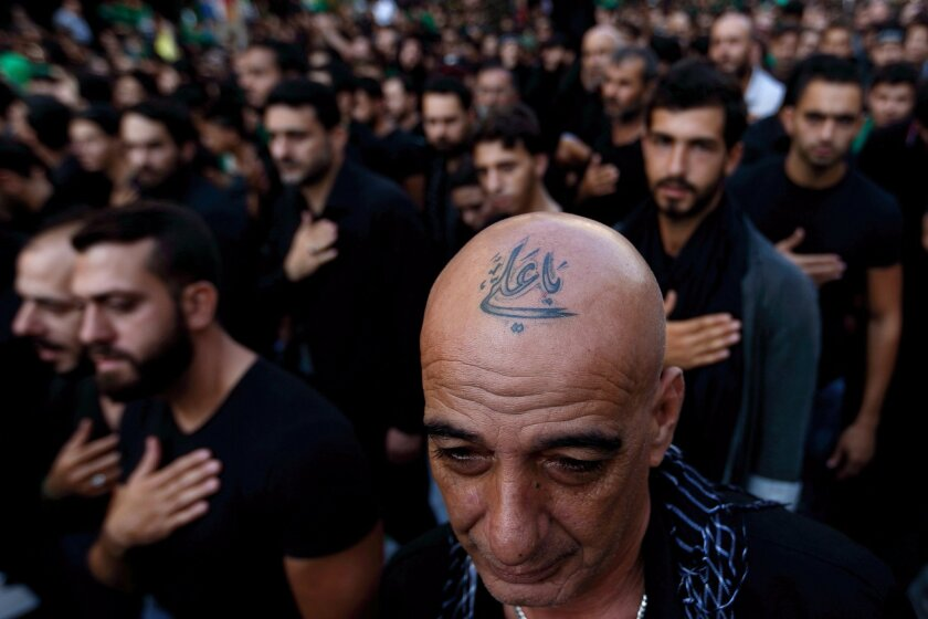 """In this Saturday, Oct. 24, 2015 photo, a Lebanese Shiite supporter of Hezbollah with a tattoo on his head that reads in Arabic, """"Oh Ali"""", beats his chest during the holy day of Ashoura, in the southern suburb of Beirut, Lebanon. A growing number of Shiite Muslims in Lebanon are getting tattoos with religious and other Shiite symbols since the civil war in neighboring Syria broke out five years ago, fanning sectarian flames across the region. (AP Photo/Hassan Ammar)"""