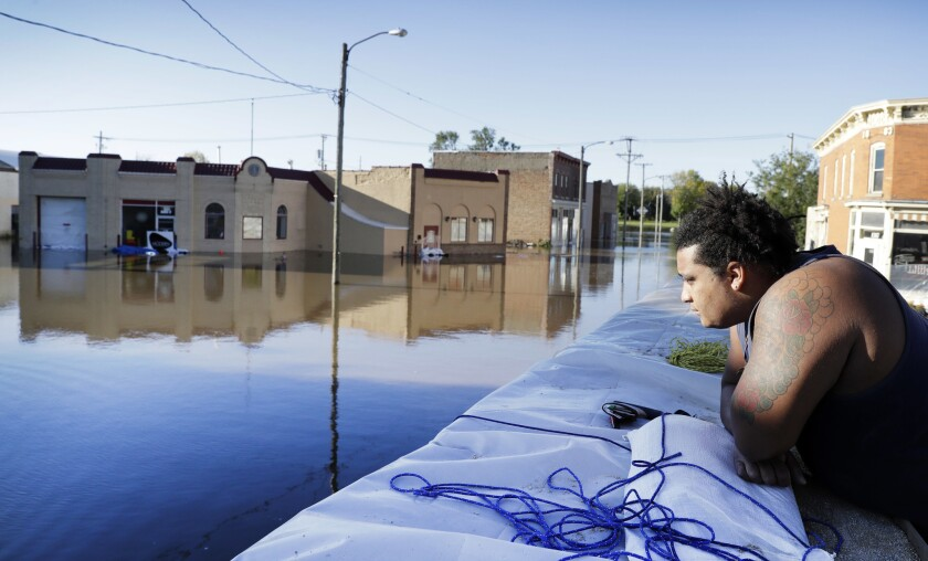 Cory Harrison stands on a flood wall as he looks over businesses flooded by the Cedar River on Sept. 27 in Cedar Rapids, Iowa.