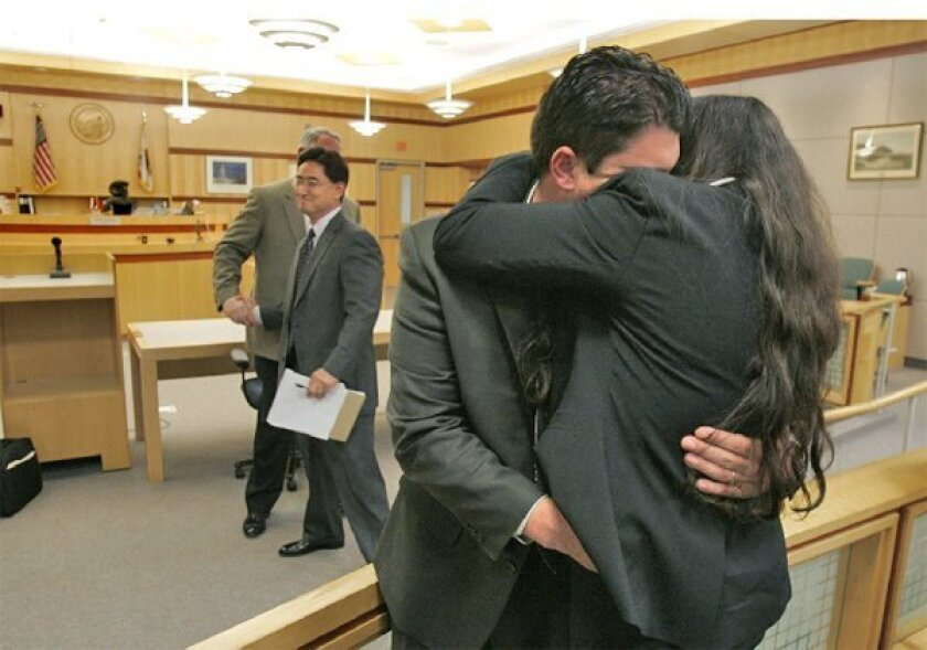 San Diego police Officer Frank White embraced his wife, Jacquellyn, after he was found not guilty of two counts in the March 2008 shooting of another motorist and her son. (Charlie Neuman / Union-Tribune)