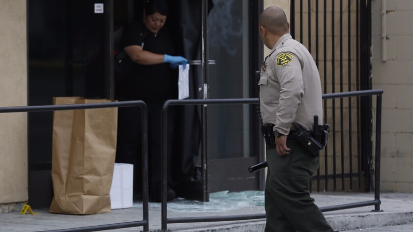 Members of the Los Angeles County Sheriff's Department collect evidence at a marijuana dispensary in Walnut Park in June. The shop's owner shot and wounded two men trying to rob the store, authorities said.