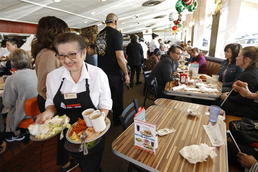 Waitress Sonia Bernal clears plates from a table at Norms in West Hollywood.