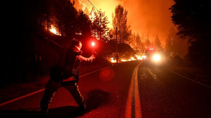 Cal firefighter Tyler Benson throws a flare to start a back fire as the the Delta Fire burns along Pollard Camp Road north of Redding, California.