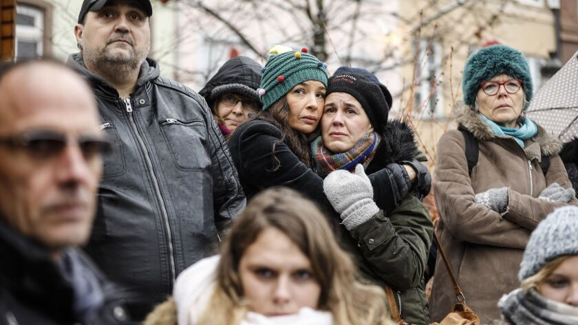 Residents react during a gathering being held in a central square of the eastern French city of Stra