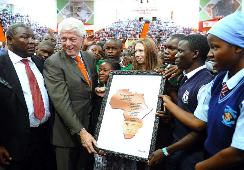 Former President Clinton receives an award certificate from students on Saturday in Nairobi.