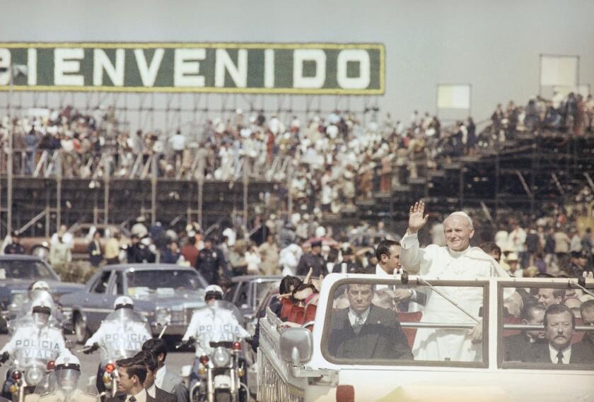 El papa Juan Pablo II saluda a los fieles durante un recorrido por la Ciudad de México el 25 de enero de 1979. Juan Pablo visitó cinco veces el país y conquistó los corazones de los mexicanos, que ahora se aprestan a recibir a Francisco, un pontífice más liberal y que habla con mucha franqueza de los problemas mundiales. (AP Photo, File)