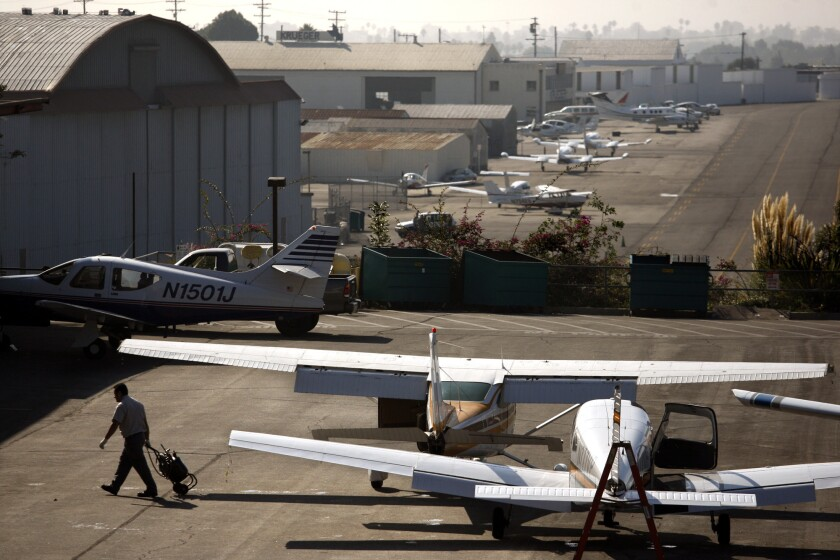 A mechanic walks away from parked planes at Santa Monica Airport. A new legal skirmish has erupted over a proposal ballot measure that would require voters to approve any land use change at the airport.