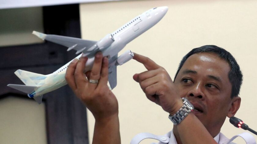 Indonesian National Transportation Safety Committee investigator Nurcahyo Utomo holds a Boeing 737 aircraft model as he answers questions from journalists.