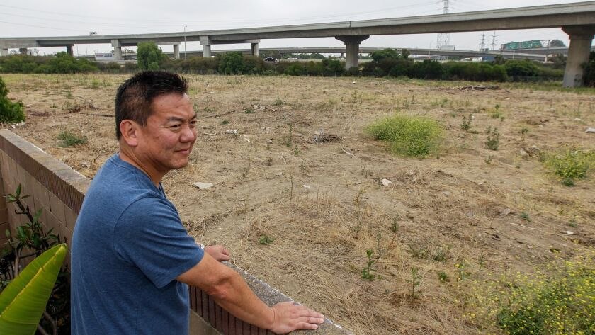 Harbor Gateway resident Craig Kusunoki looks at the site of a proposed 15-unit housing development next to the interchange of the 110 and freeways. Kusunoki and his neighbors say it would put housing too close to the interchange and a nearby freeway ramp.