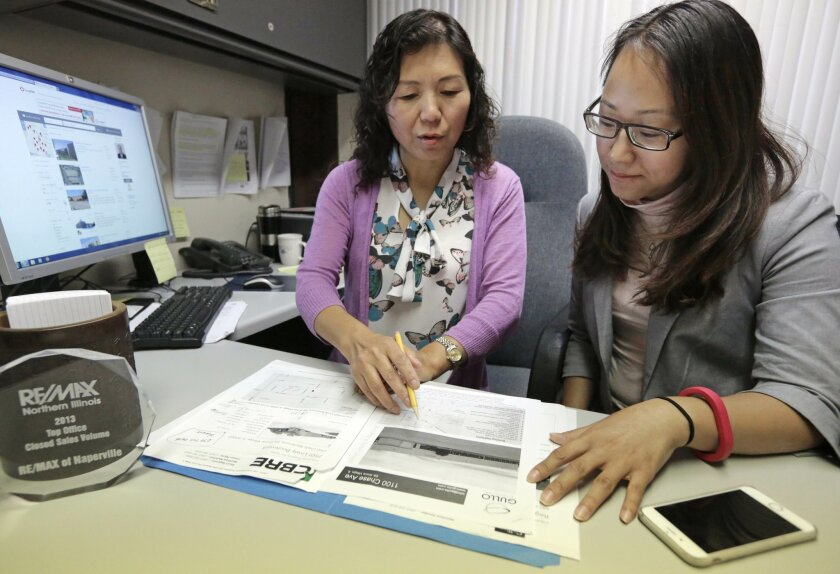 In this Wednesday, Sept. 16, 2015 photo, Shanshan Wu, right, goes over real estate listings with her broker, Lisa Li, in Naperville, Ill. Wu, who already owns three houses back home in China, has spent the last two months in Chicago shopping for a three-bedroom home, and she's not done. Chinese have been snapping up U.S. real estate of all kinds, looking for a safer place to put their money than their own slowing economy. (AP Photo/M. Spencer Green)