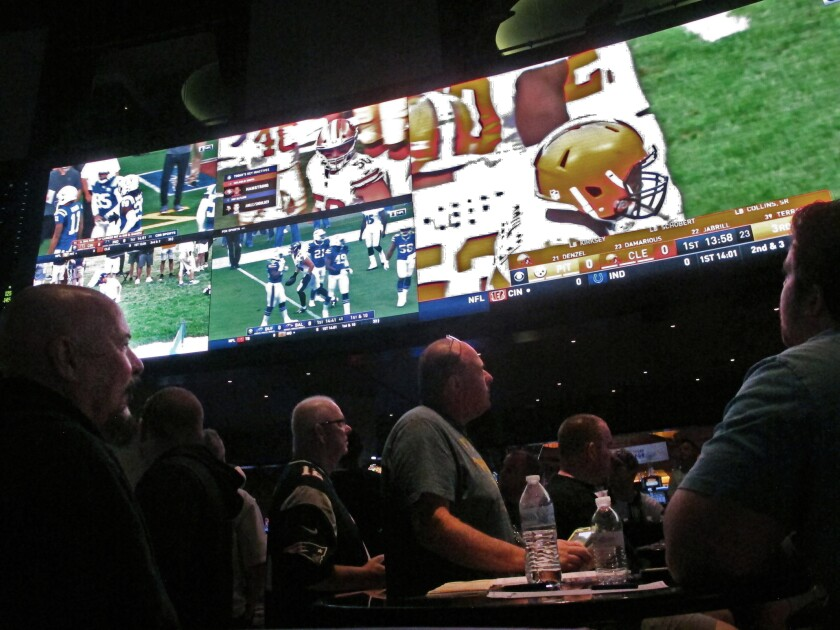 """FILE — In this Sept. 9, 2018 file photo, customers watch an NFL game in a sports betting lounge, in Atlantic City, N.J. New Jersey's top gambling regulator is threatening to fine sports books operating in his state that ask customers to cancel requests to cash out money from their accounts, saying the practice is ongoing and """"unacceptable.""""(AP Photo/Wayne Parry, File)"""