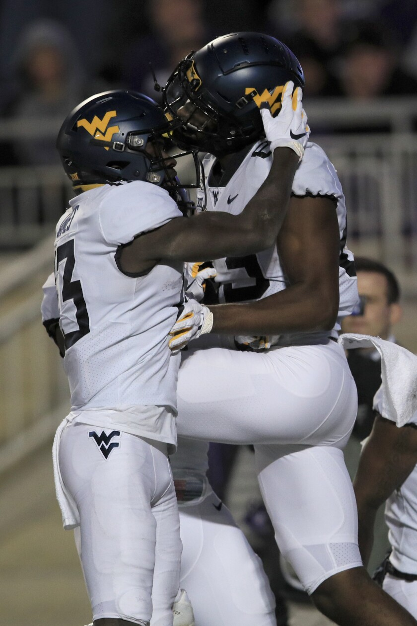 West Virginia wide receiver Sam James (13) congratulates fellow wide receiver Bryce Wheaton (83) after a touchdown during the second half of an NCAA college football game against Kansas State in Manhattan, Kan., Saturday, Nov. 16, 2019. (AP Photo/Orlin Wagner)