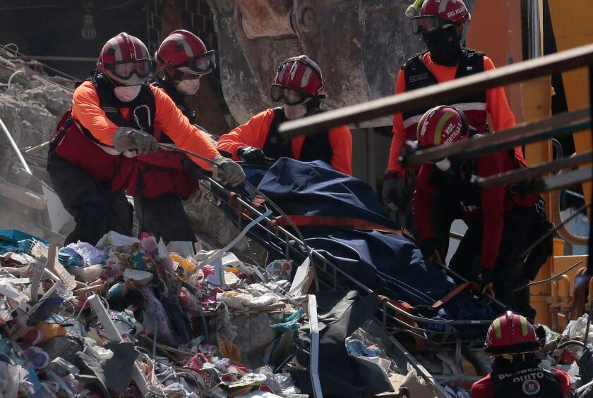 Rescuers remove a corpse from the rubble in Manta, Ecuador, on Wednesday.