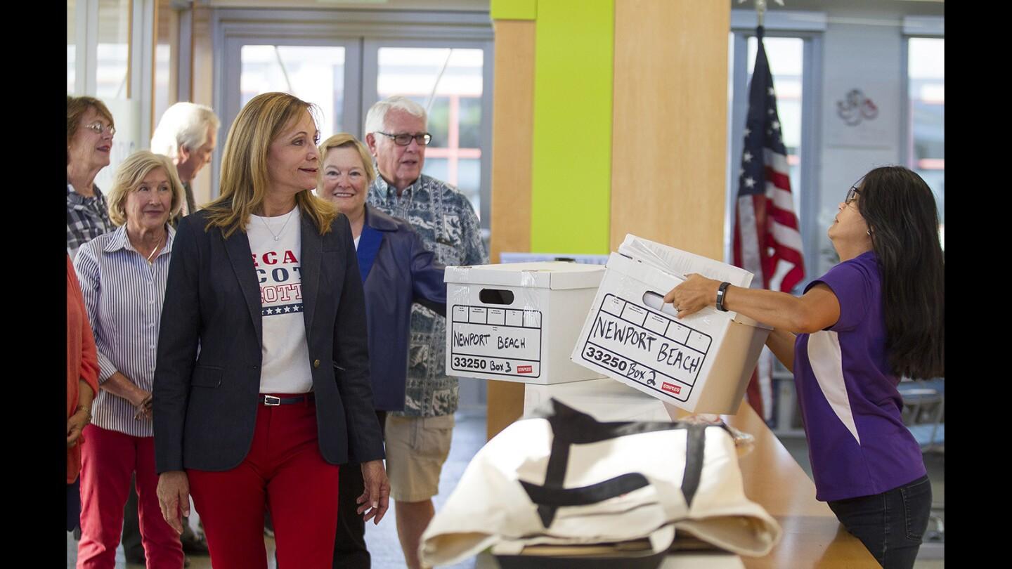 Lynn Swain, left, watches as Leilani Brown, the city clerk for Newport Beach, takes a box filled with petitions by people who want to recall Newport Beach City Councilman Scott Peotter at city hall on Friday, October 27.