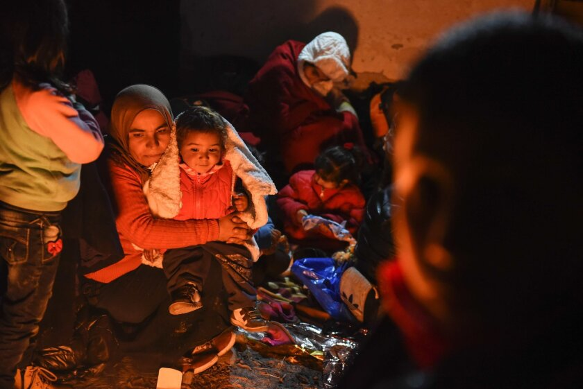 Migrants and refugees warm up around a bonfire after crossing the Greek-Macedonian border as they wait to enter a refugee camp on Dec. 6.
