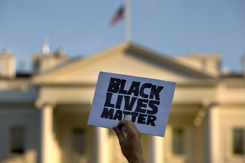 """A man holds up a sign saying """"black lives matter"""" during a protest of shootings by police, in Washington, Friday, July 8, 2016, by the White House. In the span of four days, the United States has had to come to terms with the deaths of two black men at the hands of police - the first caught on vide"""