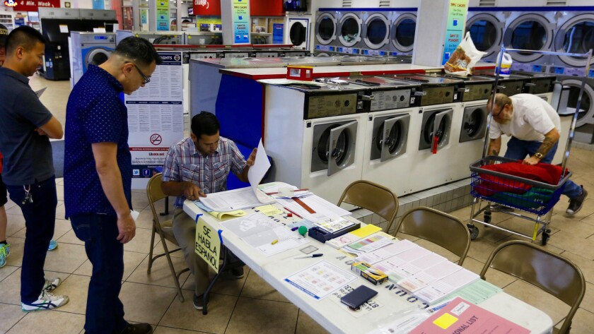 Voters line up at 7 a.m. to cast their ballots at the Super Suds Laundromat in Long Beach.