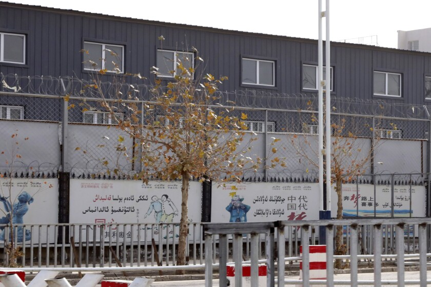"""FILE - In this Dec. 5, 2018, file photo, two layers of barbed wire fencing ring the """"Hotan City apparel employment training base"""" where Hetian Taida Apparel Co. has a factory in Hotan in western China's Xinjiang region. The Trump Administration is blocking shipments from Chinese company Hetian Taida Apparel, which makes baby pajamas sold at Costco warehouses, after the foreign manufacturer was accused of forcing ethnic minorities locked in an internment camp to sew clothes against their will. (AP Photo/Ng Han Guan, File)"""