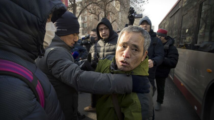 Plainclothes security officials take away a supporter of Chinese human rights lawyer Wang Quanzhang near the Secondary Intermediate People's Court of Tianjin on Dec. 26.