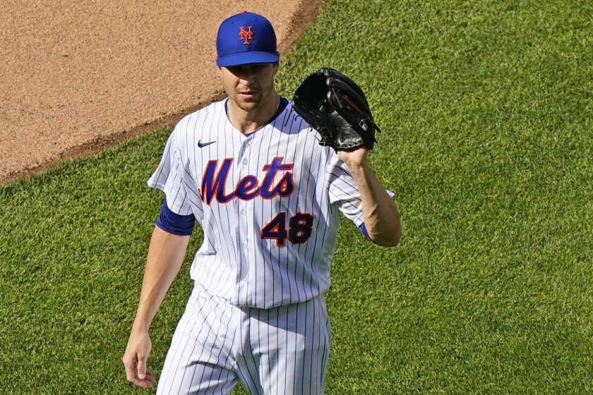 New York Mets starting pitcher Jacob deGrom shows his glove to the home plate umpire before taking the mound during the first inning of a baseball game against the Atlanta Braves, Monday, June 21, 2021, in New York. (AP Photo/Kathy Willens)