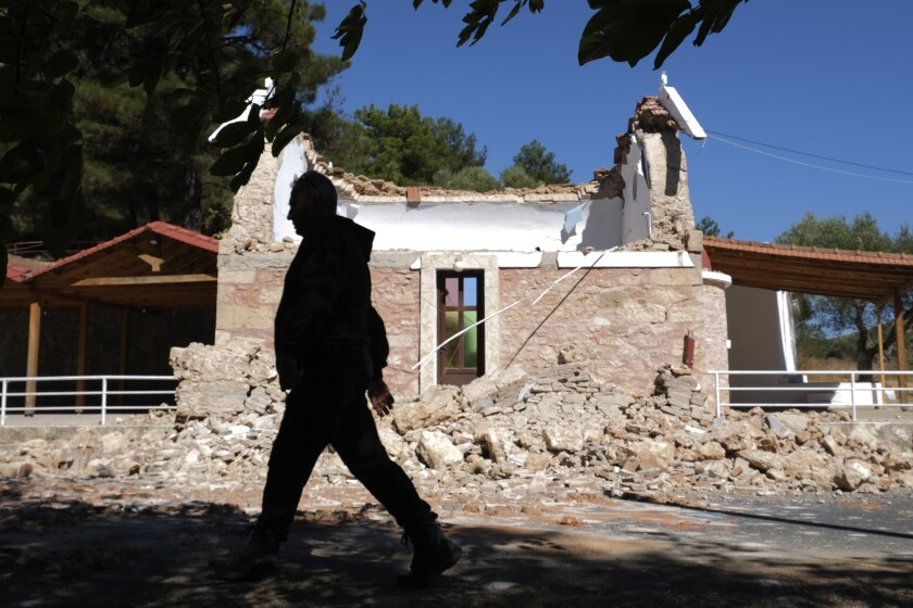 A Resident passes next to a damaged Greek Orthodox chapel after a strong earthquake in Arcalochori village on the southern island of Crete, Greece, Monday, Sept. 27, 2021. A strong earthquake with a preliminary magnitude of 5.8 has struck the southern Greek island of Crete, and Greek authorities say one person has been killed and several more have been injured. (AP Photo/Harry Nikos)