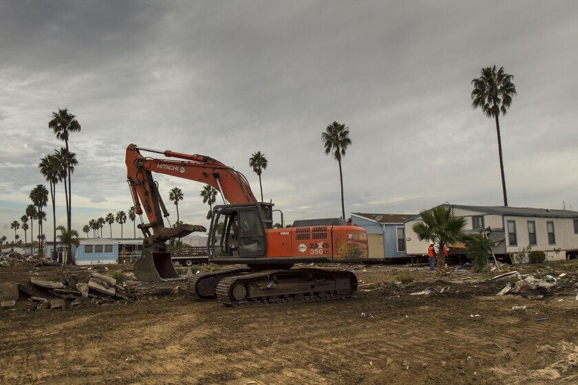 An excavator cleans up debris at the Marina Park mobile home park on Wednesday, December 18. (Scott Smeltzer, Daily Pilot)