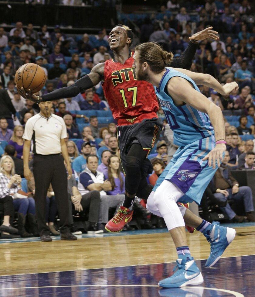 Atlanta Hawks' Dennis Schroder (17) drives past Charlotte Hornets' Spencer Hawes (00) in the first half of an NBA basketball game in Charlotte, N.C., Sunday, Nov. 1, 2015. (AP Photo/Chuck Burton)