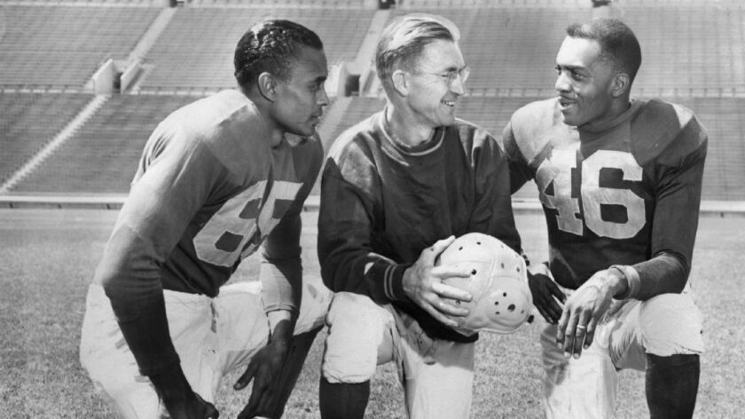 Ex-UCLA Bruins Woody Strode, left, and Kenny Washington, right, listen to Los Angeles Rams Coach Adam Walsh in publicity photo taken at the Los Angeles Memorial Coliseum.