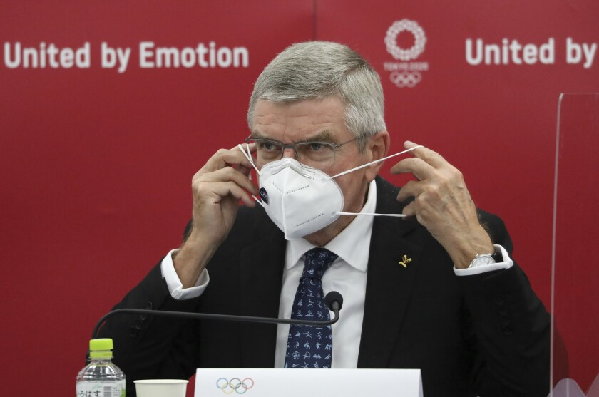 Thomas Bach, International Olympic Committee (IOC) President, puts on his mask before speaking during the joint press conference between IOC and Tokyo Organizing Committee of the Olympic and Paralympic Games (Tokyo 2020) in Tokyo, Japan, Nov. 16, 2020. Olympic participants and fans arriving for next year's postponed Tokyo Olympics are likely to face requirements to be vaccinated to protect the Japanese public, Bach said Monday after meeting with new Prime Minister Yoshihide Suga. (Du Xiaoyi/Pool Photo via AP)