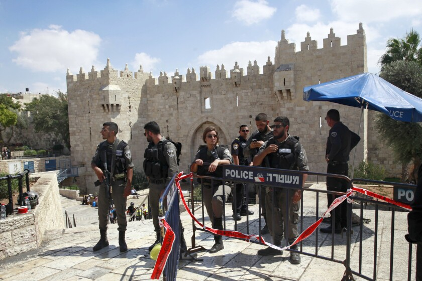 Israeli border police officers stand near the scene where, authorities say, a Jordanian national was shot and killed after he tried to stab officers in Jerusalem's Old City.