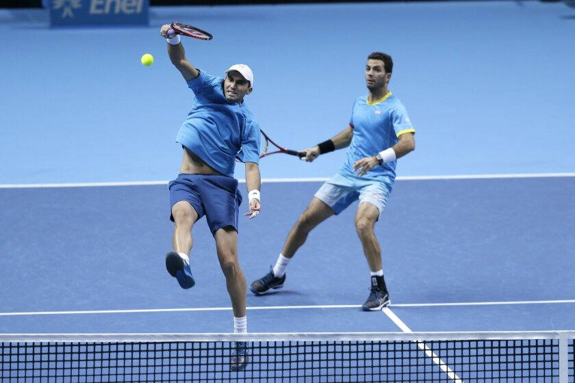 Netherlands' Jean-Julien Rojer, right, watches as Romania's Horia Tecau plays a return to United States's Bob Bryan and Mike Bryan during their ATP World Tour Finals tennis semifinal doubles match at the O2 Arena in London, Saturday Nov. 21, 2015. (AP Photo/Tim Ireland)