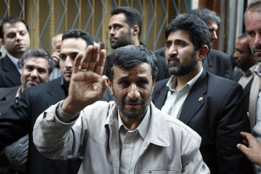 Escorted by his bodyguards, Iranian President Mahmoud Ahmadinejad, center, waves to his well wishers, as he leaves at the conclusion of an electoral campaign meeting for June 12 presidential elections, in Tehran, Iran, Sunday, May 31, 2009. Ahmadinejad faces a tough battle against reformists who ha