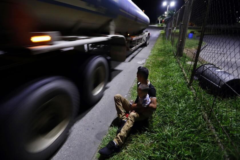 SAN PEDRO SULA, HONDURAS--NOV.7, 2018--Elminton Hernandez, age 26, holds his son Axel, age 2, at the