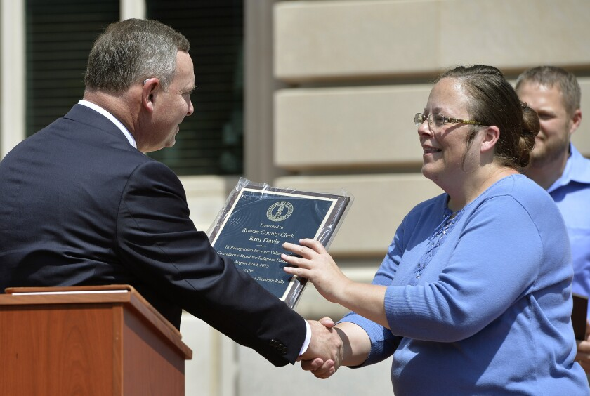 Pastor Jeffrey Fugate gives an award to Rowan County Clerk Kim Davis during a Religious Freedoms Rally at the Kentucky State Capitol on Aug. 22. Davis has been sued by The American Civil Liberties Union for denying marriage licenses to same-sex couples.