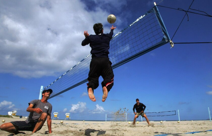 Enjoying blue skies and sunshine, volleyball players (from left) Mike Kuerbis, Linn  Holland (jump), and Kevin Kuerbis work on their skills at the south end of Mission Beach. Photo by Eduardo Contreras/San Diego Union-Tribune
