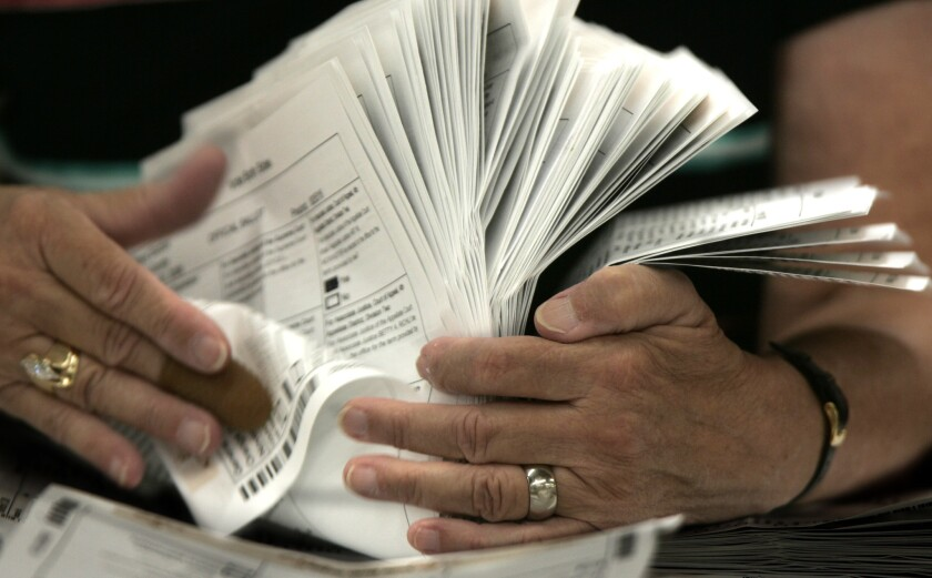 An election worker in Santa Ana with a stack of absentee ballots. A new California state law will shift millions more voters to casting ballots by mail as soon as next year.