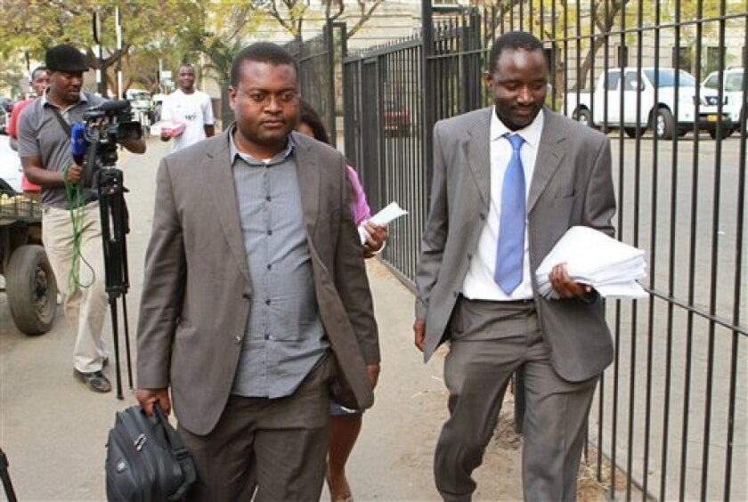 Chris Mhike, right, Morgan Tsvangirai's lawyer, arrives at the Constitutional Court accompanied by Alex Magaisa, Tsvangirai's legal advisor, in Harare, Friday, Aug. 9, 2013. Mhike made an application in the Constitutional Court challenging the results of the presidential elections which saw President elect Robert Mugabe receiving more than 60 percent of the vote with his main challenger Morgan Tsvangirai declaring the election null and void. (AP Photo/ Tsvangirayi Mukwazhi)