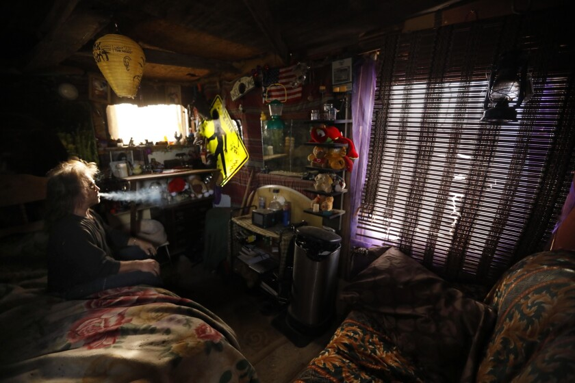 LANCASTER, CA - NOVEMBER 27, 2018 - - Steve Novak, 52, enjoys a smoke in the small cabin he construc