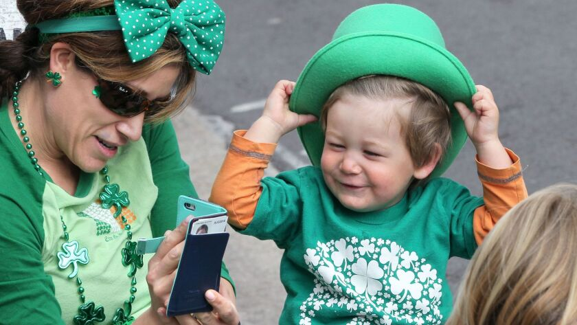 Erin Berard takes a photo of her son Dyla Patrick as they wait for the start of the San Diego St. Patrick's Day Parade.