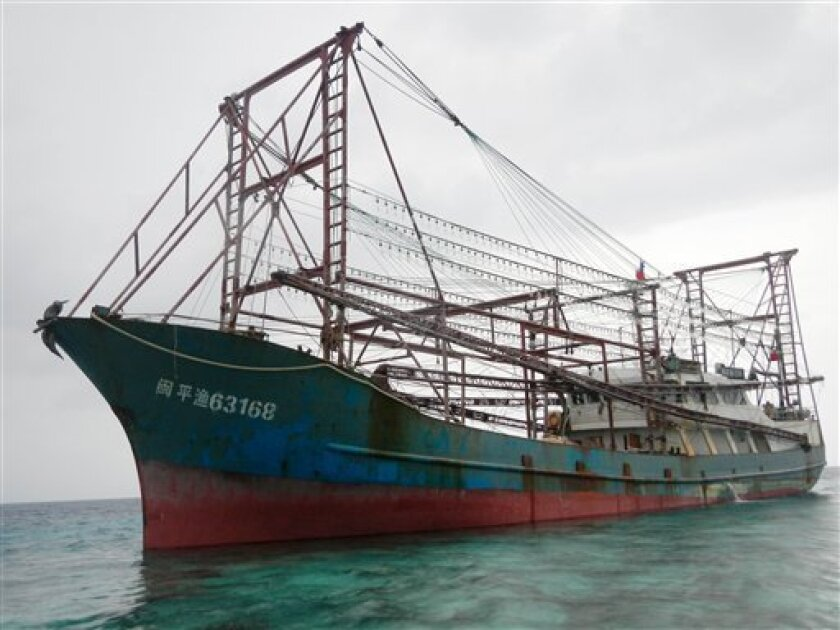 In this photo taken April 9, 2013 and released by the Philippine Coast Guard, a Chinese fishing vessel is stranded after it ran aground on the Tubbataha reefs, a UNESCO World Heritage site, in the Sulu Sea in Palawan province, southwestern Philippines. The vessel with 12 crewmen ran aground in the protected coral reef, where a U.S. Navy minesweeper got stuck and had to be dismantled recently, officials said. (AP Photo/Philippine Coast Guard) NO SALES