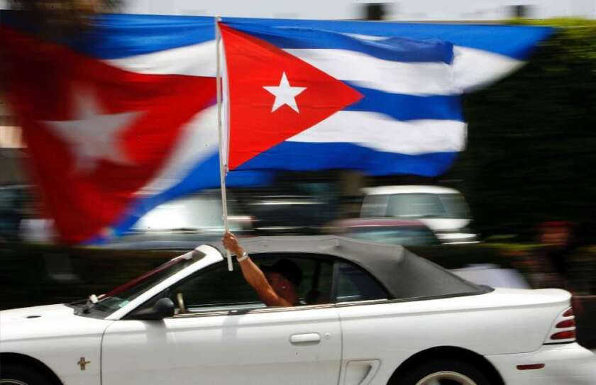 A motorist waves a Cuban flag in Miami's Little Havana neighborhood. Recent polls have shown that Americans are more open to normalizing relations with Cuba.