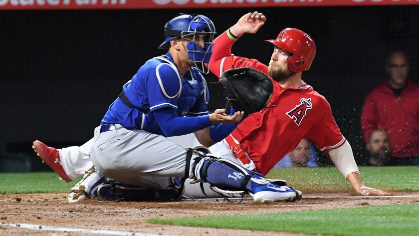 Angels' Kevan Smith beats the tag of Dodgers catcher Austin Barnes during the Freeway Series on Monday in Anaheim.