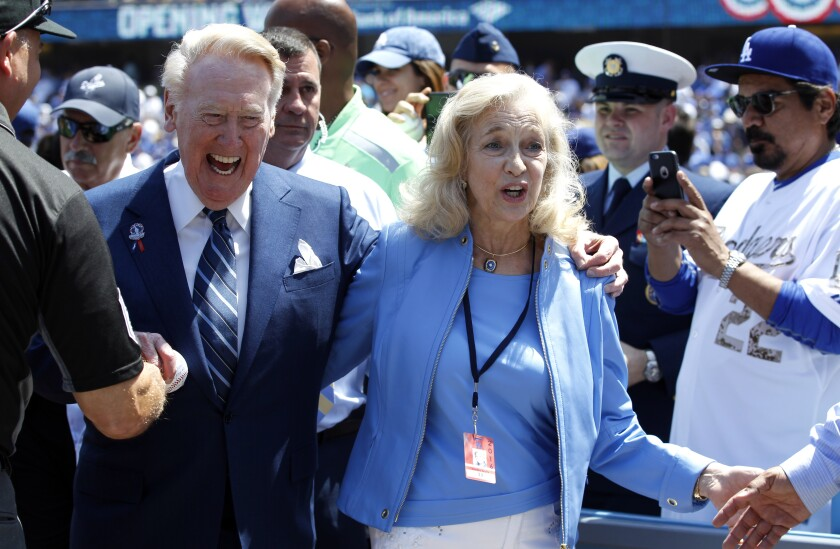 Dodgers announcer Vin Scully with his wife, Sandi, leave the field.